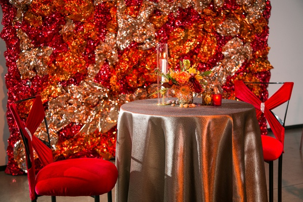sweetheart table with red chairs, backdrop of foil made to look like fire