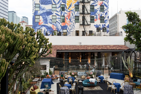 wedding reception lounge area outdoor hotel figueroa mural on back of building backdrop tropical