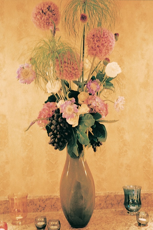Tall flower centerpiece with grapes and pink flowers