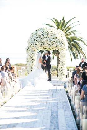 White wash wood aisle plank runner candles along side white flower arch chuppah design palm trees