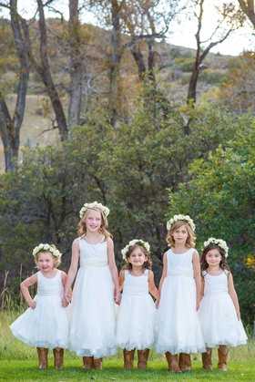 Five flower girls wearing white dresses with flower crowns and brown cowboy boots Aspen wedding