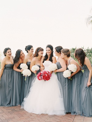 bride in white vera wang ballgown laughs with bridesmaids in long gray grey dresses and bouquets