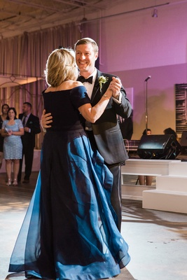 groom dances with his mom in blue dress