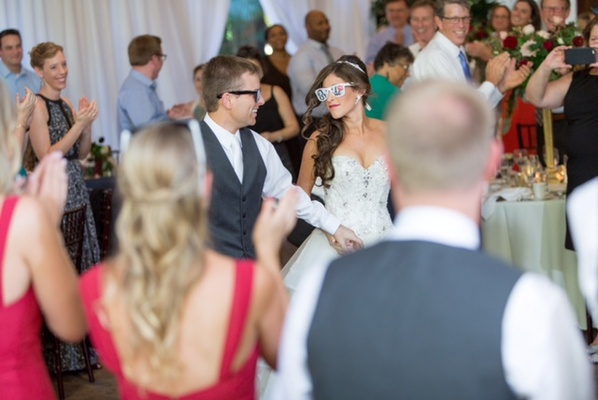 bride in alfred angelo gown, groom in dark navy grey suit vest grand entrance novelty sunglasses
