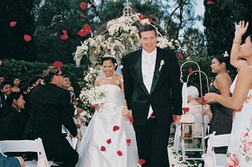 Guests toss rose petals at couple after outdoor ceremony