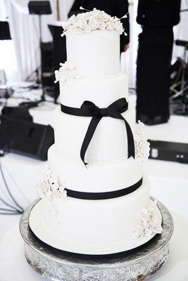 five-tiered wedding cake with white flowers and black ribbon