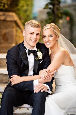 bride in strapless ines di santo wedding dress updo hairstyle veil groom in tuxedo bow tie