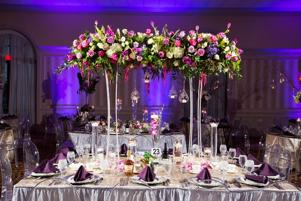 Wedding reception silver linens purple uplighting tower suspended flower arrangement glass orb