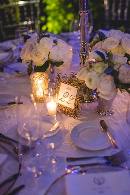 Wedding reception purple lighting white flowers gold ornate frame for number candles