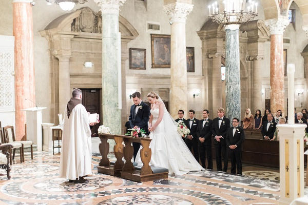 Bride and groom at altar wedding ceremony marble columns st andrew's catholic church traditional