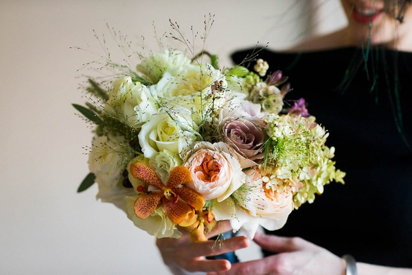 Bridal bouquet of white roses, lisianthus, orange Mokara orchids, garden roses, green hydrangeas