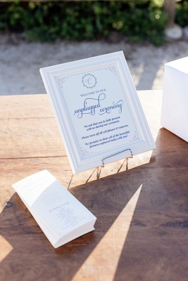 Wood table with ceremony programs and unplugged wedding ceremony sign in frame on stand