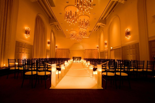 Indoor wedding with candle-lined aisle runner