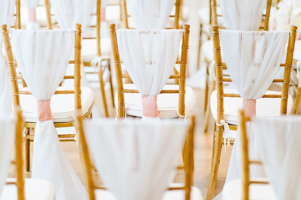 Gold chair back with white cushions, white chair cover and pink fabric wrap