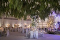 wedding reception ballroom violet lighting greenery overhead white flowers silver decor bar band