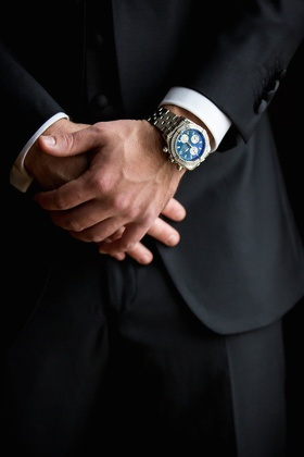 Groom in black tuxedo wears Breitling watch with a dark blue face