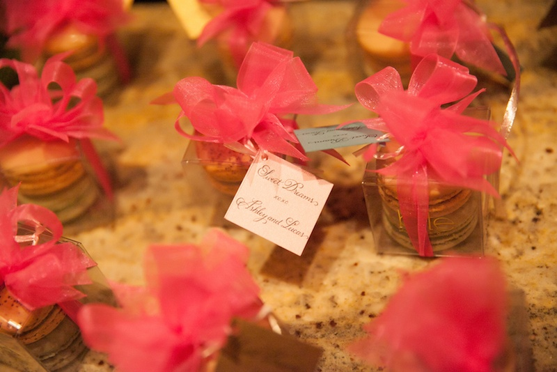 Pink ribbon bows on boxes of French macaron wedding favors