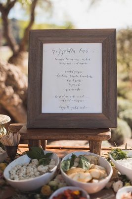 Cocktail hour mozzarella bar at outdoor wedding rustic wood frame with calligraphy sign Laura Hooper