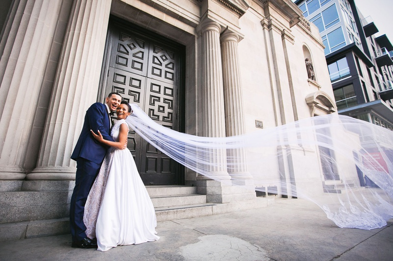 Couple in front of vibiana in downtown los angeles long cathedral veil at a former cathedral