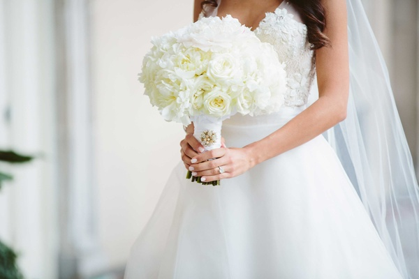 White manicure on bride holding white rose, ranunculus, and peony flowers in white pale pink center