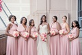 bride in strapless wedding dress curled hair necklace bridesmaids in mismatch neckline pink dresses