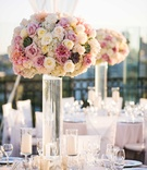 Tall wedding flower arrangement with white rose, hydrangea, pink rose, dahlia, and succulent flowers