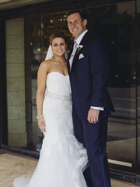 Bride in lace dress with football player groom