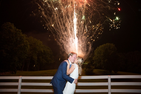 Bride in cap sleeve wedding dress groom in navy blue suit kiss during firework show at wedding recep