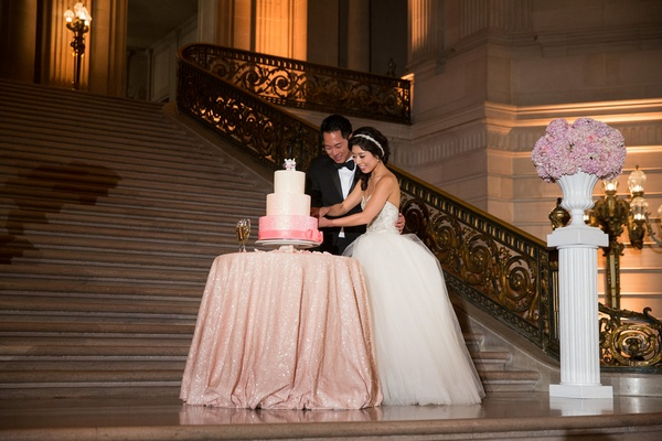 Bride in a strapless Kenneth Pool dress with tulle skirt, groom in black tux cut a pink & white cake