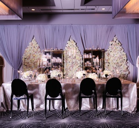 Wedding reception with long head table in silver tablecloth, black ghost chairs, floral panels