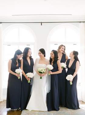 bridesmaids in dark navy blue plunging v-neck gowns white tulip bouquets