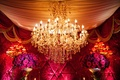 Gold and crystal chandelier above red rose centerpieces