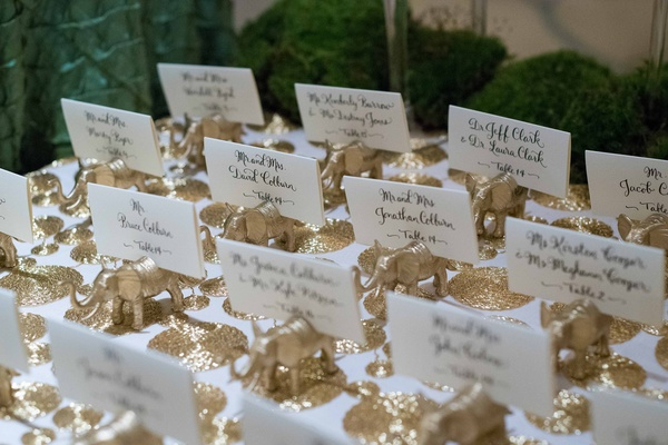 white escort cards with black calligraphy on small golden elephant figurines