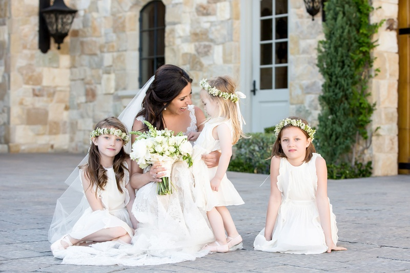 Bride in Monique Lhuillier wedding dress holding bouquet with three flower girls in flower crowns