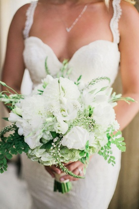 bride in galia lahav holding bridal bouquet with white flowers and greenery