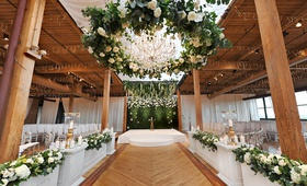 wedding ceremony wood floor aisle white boxes greenery white flowers beams wreath chandelier