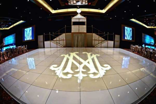 Wedding reception with a glossy tile dance floor with couple's monogram projection