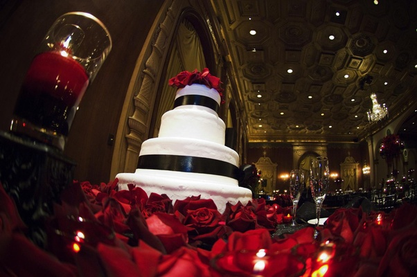 White wedding cake with black satin ribbon surrounded by red roses