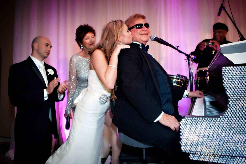 Bride kisses grandpa in law on cheek at crystal piano