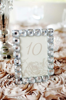 Beige flower motif table card in bling crystal frame