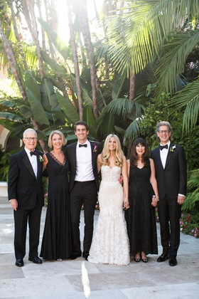 wedding photo of bride in inbal dror wedding dress groom tuxedo parents in black white attire luxury