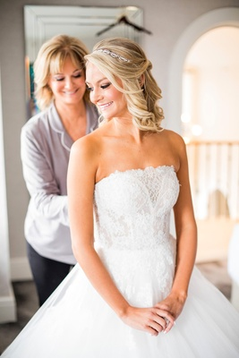 mother of the bride helps bride into strapless monique lhullier ball gown