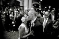 Black and white photo of bride and groom kissing in sparkler exit