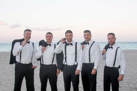 groom and groomsmen with jackets over shoulders white shirts bow ties black suspenders sunset