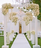White arches and roses on path to tent wedding reception