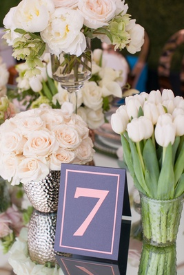 Grey and pink table number surrounded by rose tulip and peony flowers