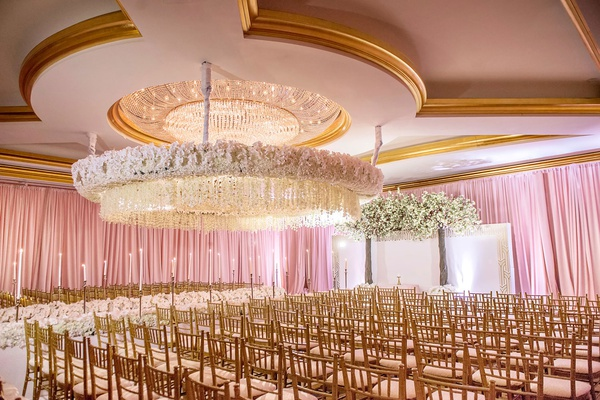 wedding ceremony ballroom gold chairs white orchid flower suspended from ceiling chandelier taper