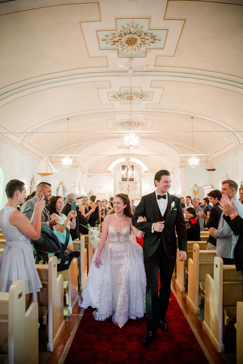 Bride in Kleinfeld Bridal beaded illusion ball gown on arm of husband in tuxedo walking up aisle