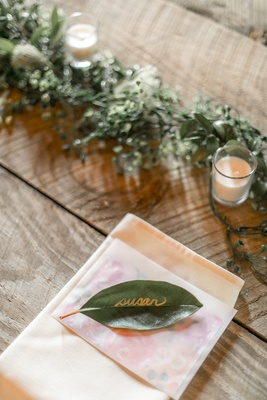 Rustic wedding with green leaf place card escort card gold calligraphy writing on napkin