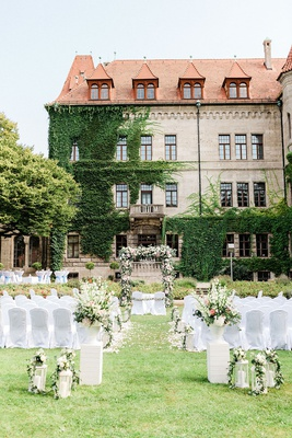 wedding ceremony germany castle venue ivy green white pink flower arrangements white chairs